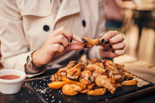 Close up of woman eating chicken wings.