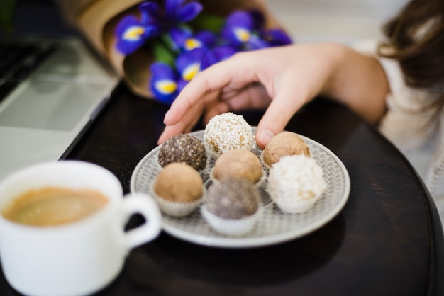 Close-up of a woman eating different type of truffles on plate