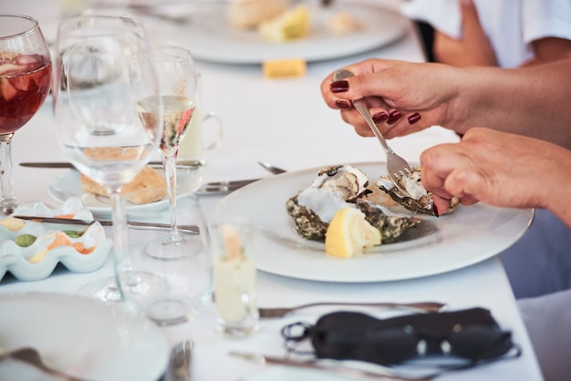 Close-up of woman eating fresh oysters in seafood mediterranean restaurant.