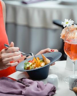 Una stretta di donna che mangia macedonia di frutta con mela, arancia, kiwi