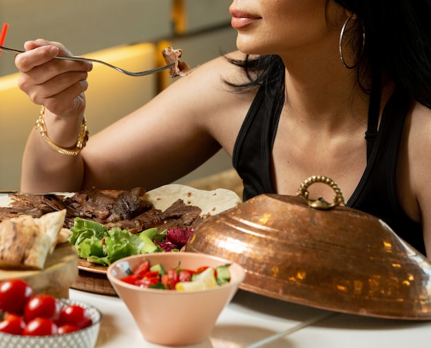 Close up of woman eating lamb doner slices served with salad and flatbread
