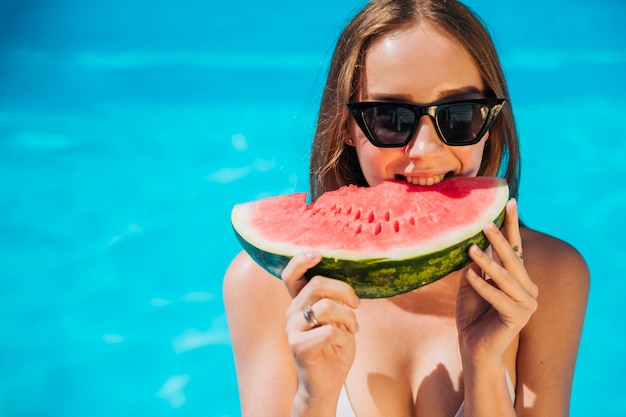 Close up woman eating watermelon in pool