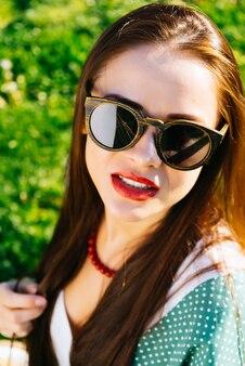 サングラス、木製のメガネ、ホワイトニングで女性の顔をクローズアップ