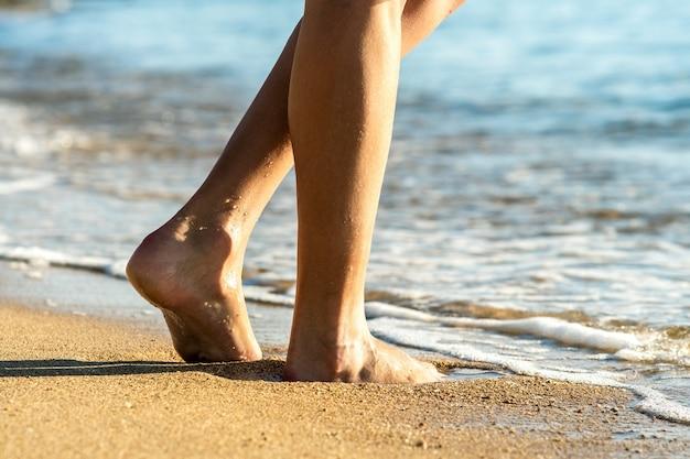 Close up of woman feet walking barefoot on sand leaving footprints on golden beach.