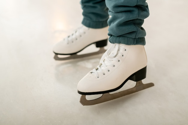Close-up of woman in figure skates learning to skate on skating rink