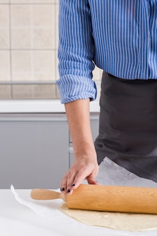 Close-up of a woman flattening the dough with rolling pin