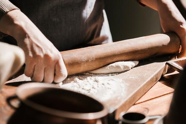 Close-up of woman flattening dough