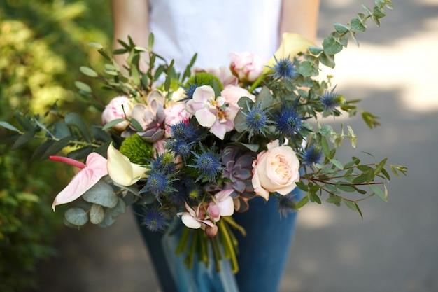 Close up woman florist decorator hold beautiful fresh flower bouquet for bride