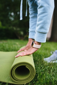 Close-up of woman folding roll fitness or yoga mat after working out in the park
