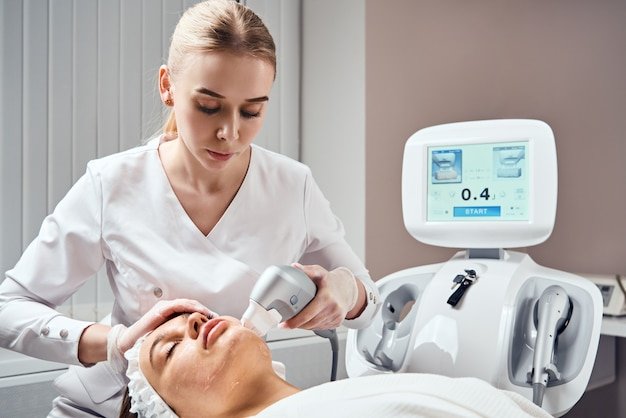 Close-up of woman getting facial hydro microdermabrasion peeling treatment