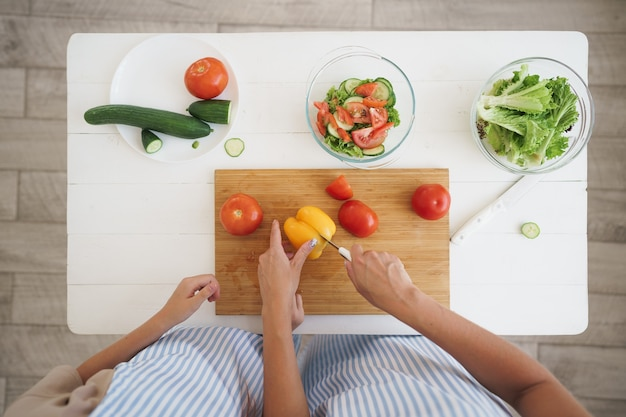 Close up of a woman and girl cutting vegetables for salad in kitchen