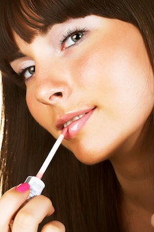 Close-up woman gloss lips over white