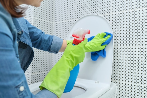 Close up of woman in gloves with rag and detergent cleaning toilet bowl, home cleaning in bathroom