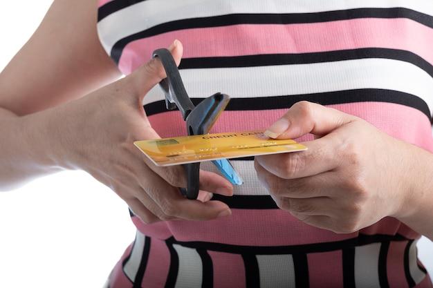 쇼핑에 대한 지출을 멈추기 위해 가위로 신용 카드를 자르는 여성의 손을 닫아라