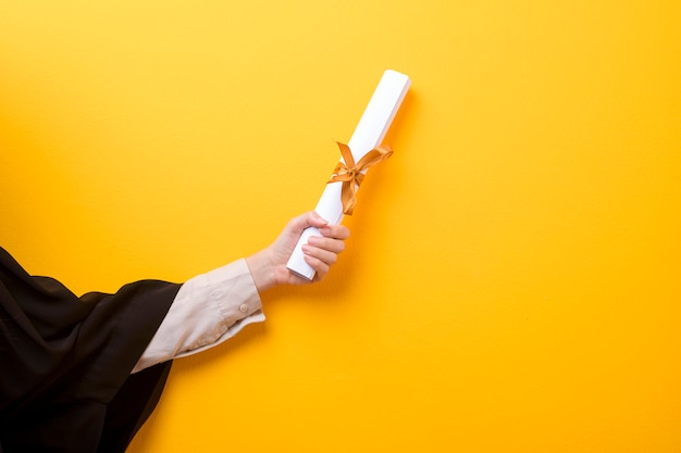 Close up of woman hand in graduation gown is holding graduation cap and certificate on yellow background