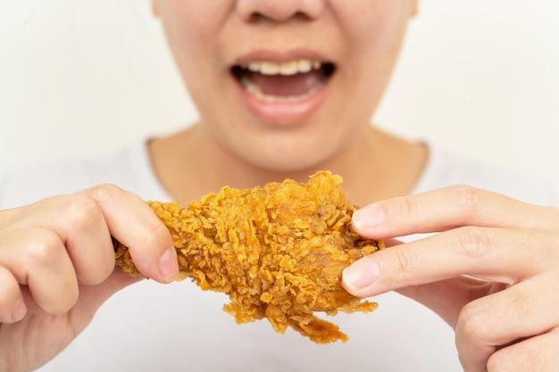 Крупным планом женщина рука держит жареную курицу для еды, женщина с концепцией быстрого питания