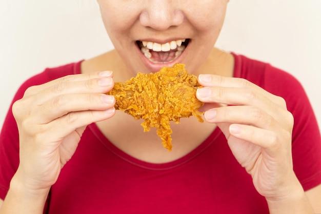 Крупным планом женщина держит жареную курицу за руку для eatwoman с концепцией быстрого питания