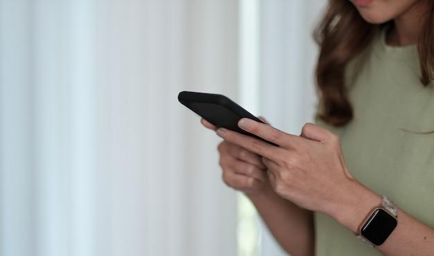 クローズアップ女性の手持ち携帯電話デバイスを使用して、作業コンセプトに関する予約スケジュールを作成します。