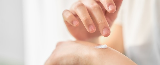 Close up of woman hand holding and applying moisturiser.