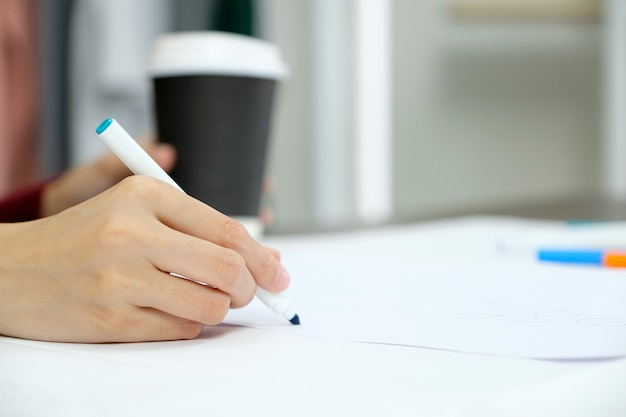 Close up of woman hand holding blue pen over white paper on table desk background