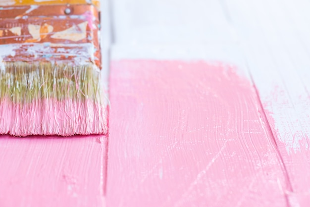 Close up woman hand holding brush painting pink color on a white wooden table.