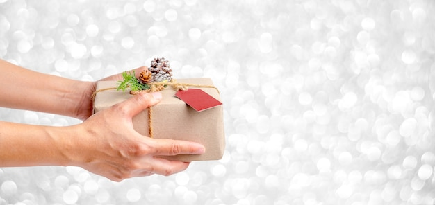 Close up woman hand holding christmas present box with silver sparkle bokeh background