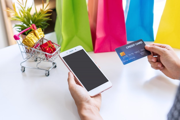 Close up of woman hand holding credit card while using smartphone with miniature gift boxes in trolley and colorful bags on white background.