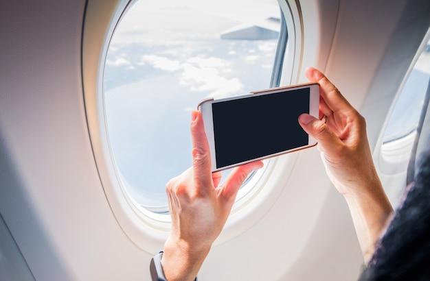 Закройте женщина рука мобильного телефона и сделать снимок за пределами