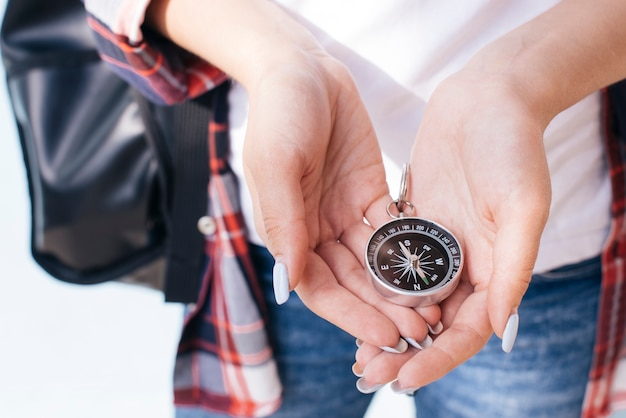 Close-up of woman hand holding navigational compass