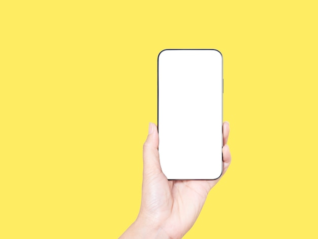Close-up of woman hand holding smartphone with blank screen, mock-up on yellow background