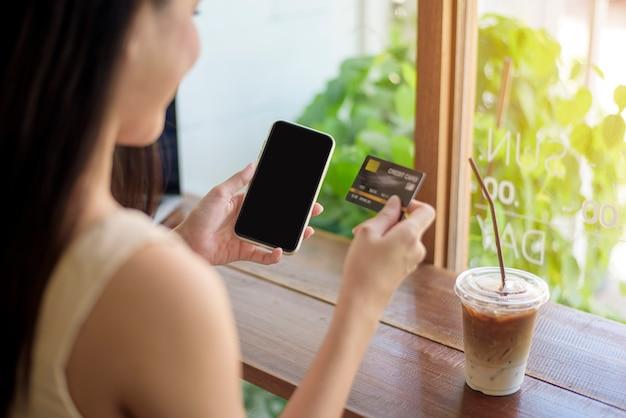 クローズアップ女性の手がクレジットカードと携帯電話を保持している、オンラインショッピングのコンセプト