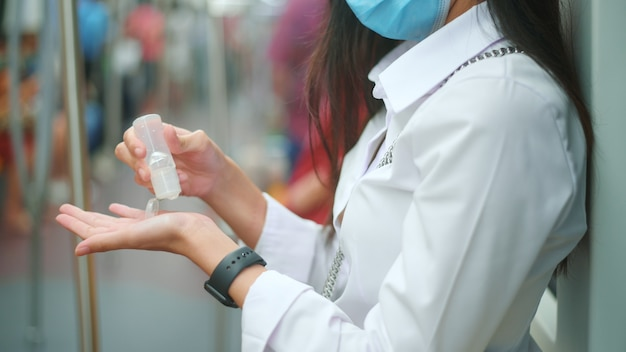 クローズアップの女性の手は、メトロでcovid-19を保護するためにアルコールジェル消毒剤を使用しています。安全輸送の概念。