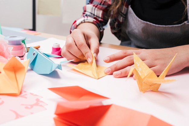 Close-up of woman hand making creative art craft using origami paper