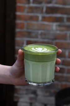 Close-up of a woman hand and matcha tea. the waiter brings drink.