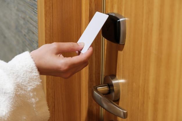 호텔에서 키 카드로 문을 여는 여자 손을 닫습니다.