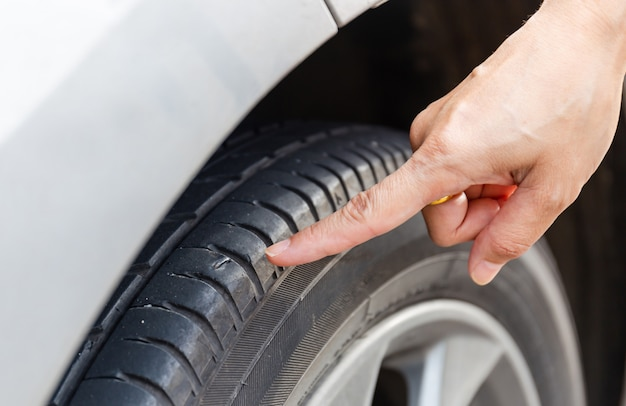Close up of woman hand poin to nail stab at the tire