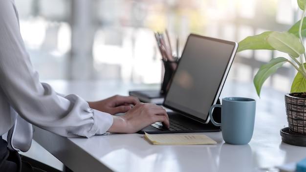 Закройте вверх. рука женщины положила на пустую клавиатуру планшета в офисе.