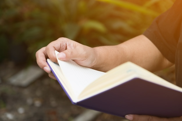 Close up of woman hand reading a book with sunlight effect