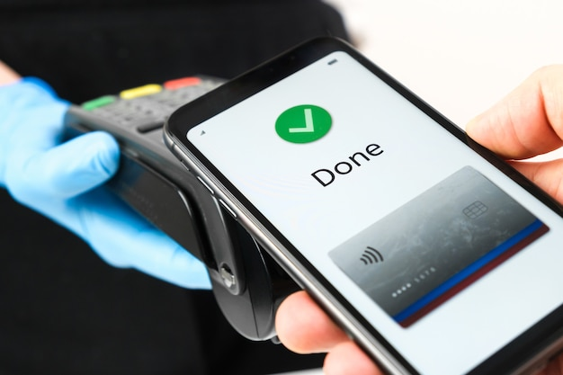 Close up of woman hand in rubber gloves holding a pos terminal or swiping machine and man hand