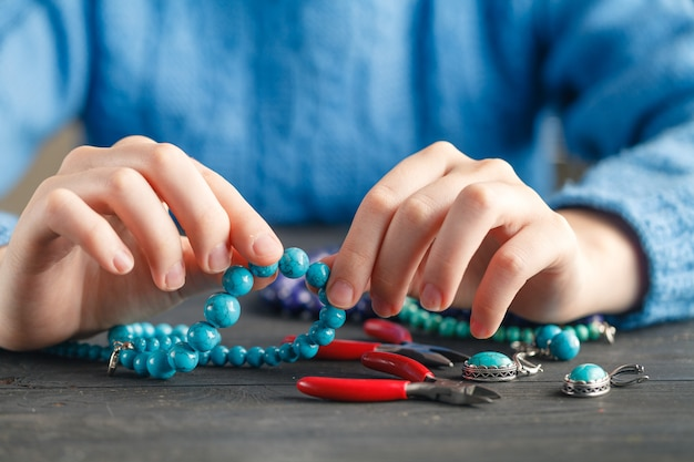 Close up of woman hand threading beads on drawstring to make artistic bead bracelet
