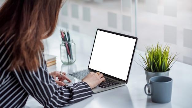 확대. 사무실에서 책상에 빈 화면이 디지털 태블릿 키보드에 입력하는 여자 손.