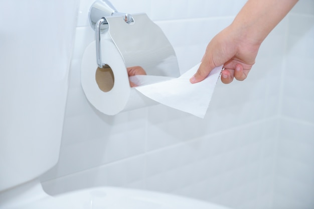 Close up of a woman hand using toilet paper in white and clean toilet room.