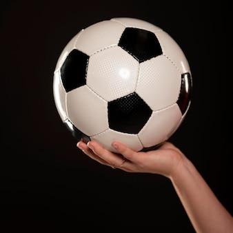 サッカーボールで女性の手を閉じる