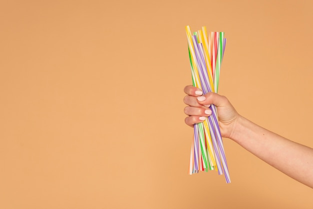 Крупным планом женская рука с пластиковыми соломинками