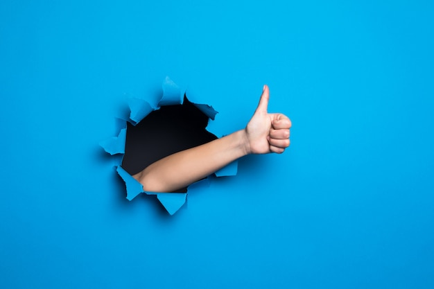 Close up of woman hand with thumbs up gesture through blue hole in paper wall.