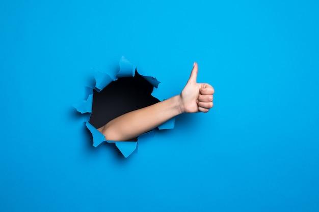 Chiuda in su della mano della donna con il pollice in alto gesto attraverso il buco blu nel muro di carta.