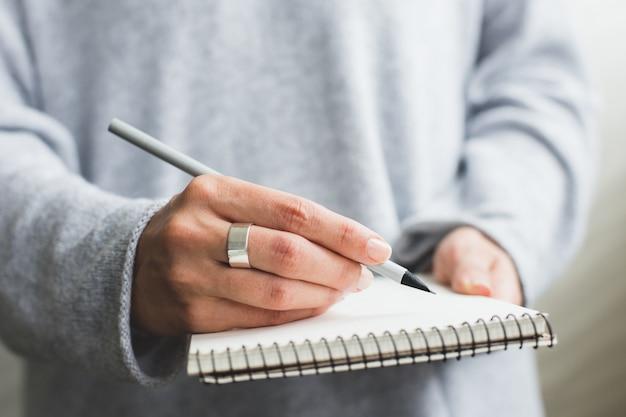Крупным планом женщина почерков на блокноте