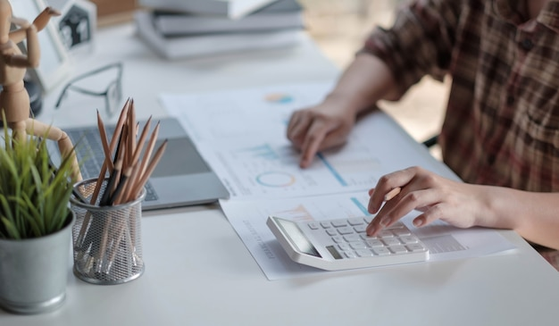 Close up woman hands of financial manager taking notes when working on report
