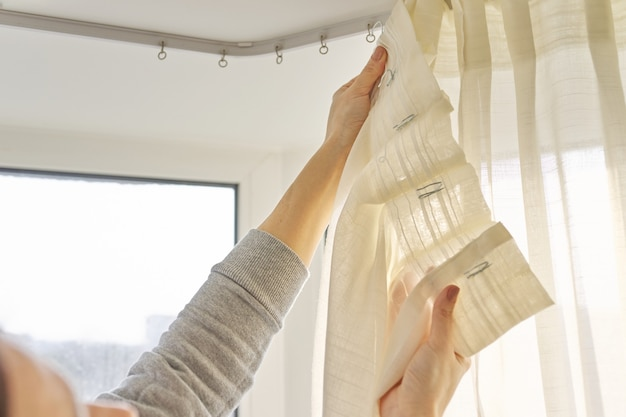 Close up of woman hands hanging curtain with metal hooks on ceiling ledge