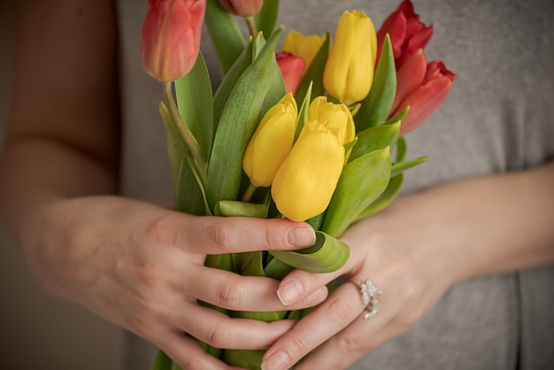 Close up woman hands holding bunch of tulip flowers